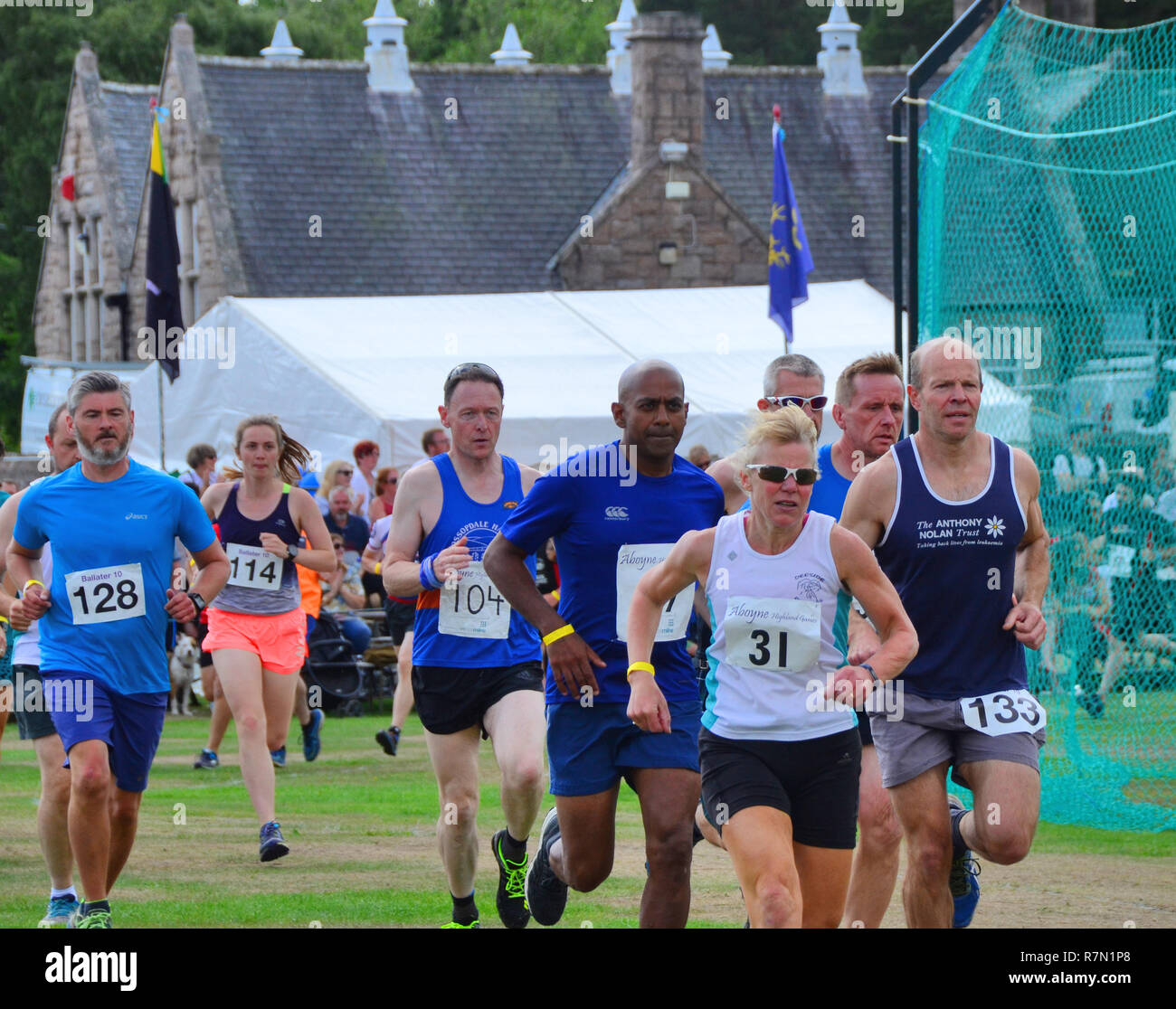 Runners returning from the hill race event at the Aboyne highland games, scotland. - Stock Image