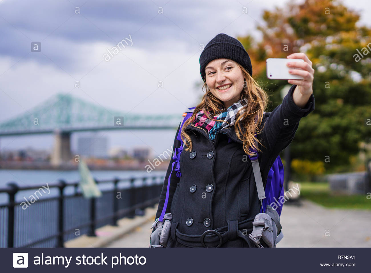 Solo woman traveller using smartphone to take selfie, Montreal, Quebec, Canada - Stock Image