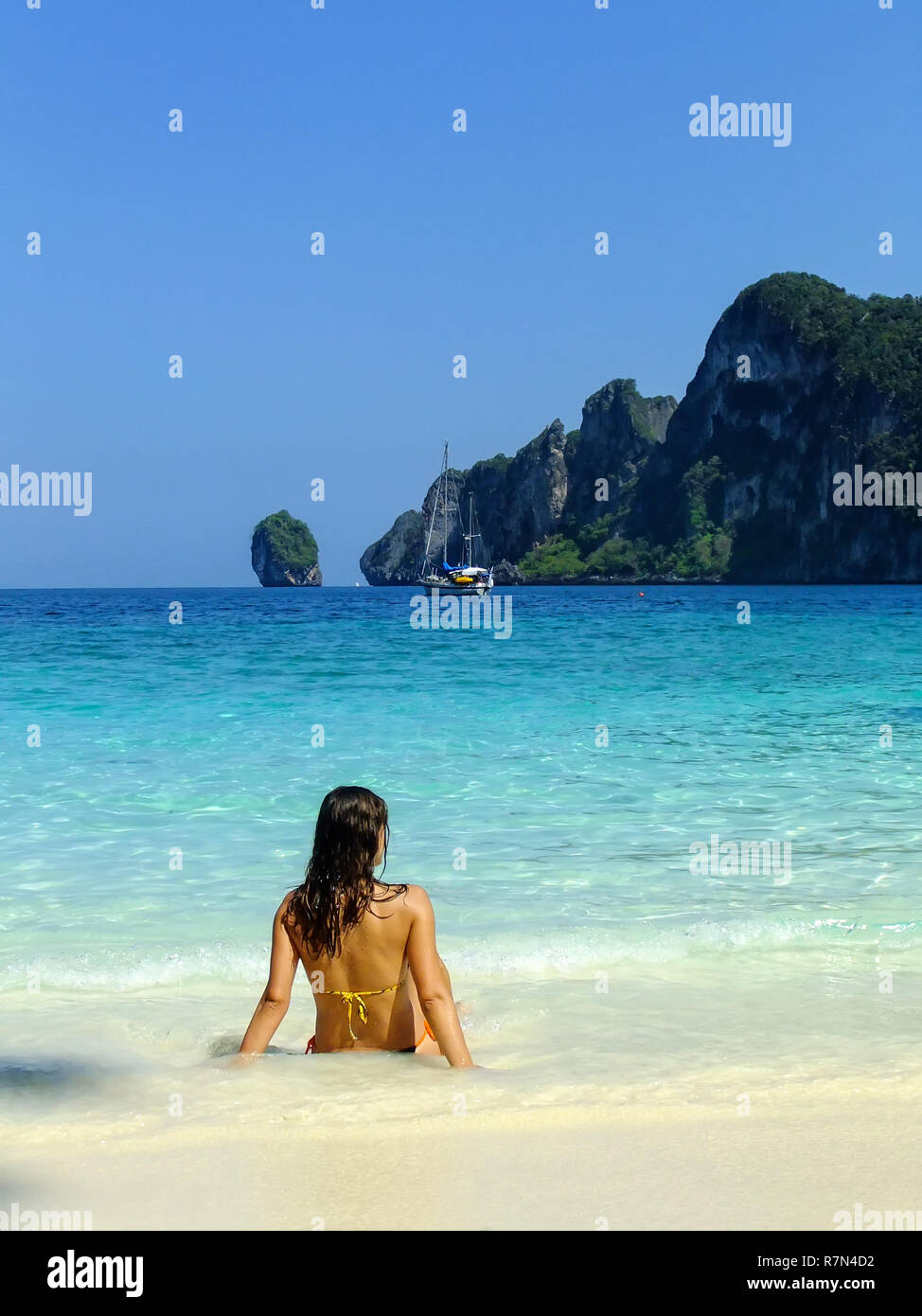 ec126b45e05d Young woman in bikini sitting at Ao Yongkasem beach on Phi Phi Don Island