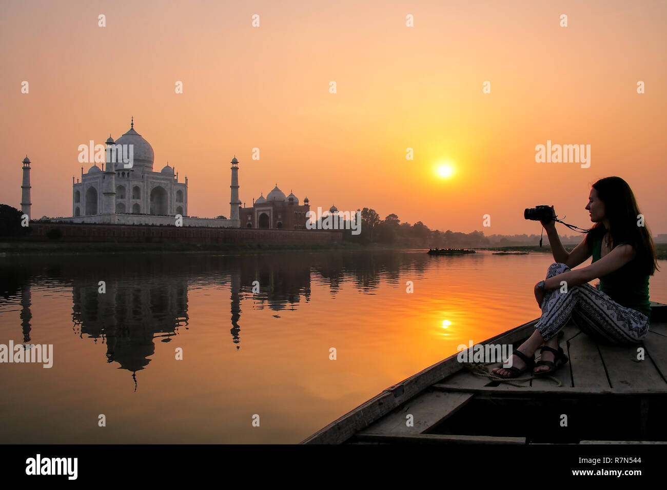 Woman watching sunset over Taj Mahal from a boat, Agra, India. It was build in 1632 by Emperor Shah Jahan as a memorial for his second wife Mumtaz Mah Stock Photo