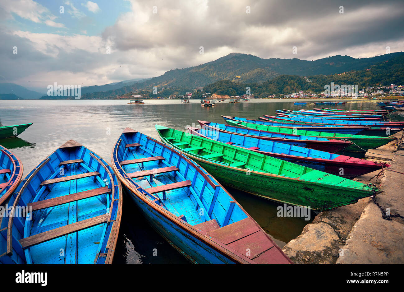 Blue and green boats at Phewa lake shore in Pokhara, Nepal. - Stock Image