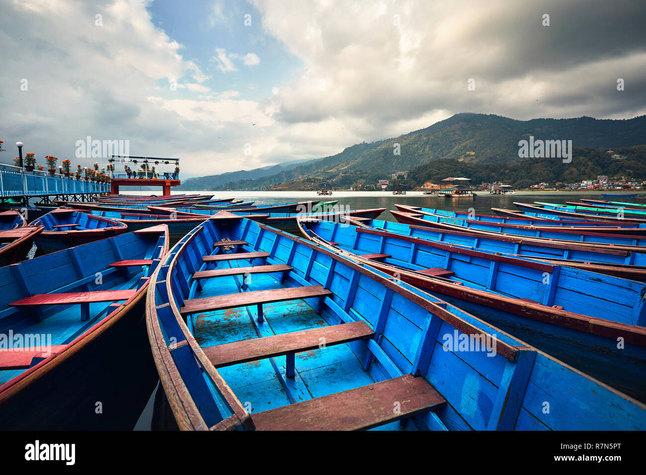 Blue boats at Phewa lake shore in Pokhara, Nepal. - Stock Image