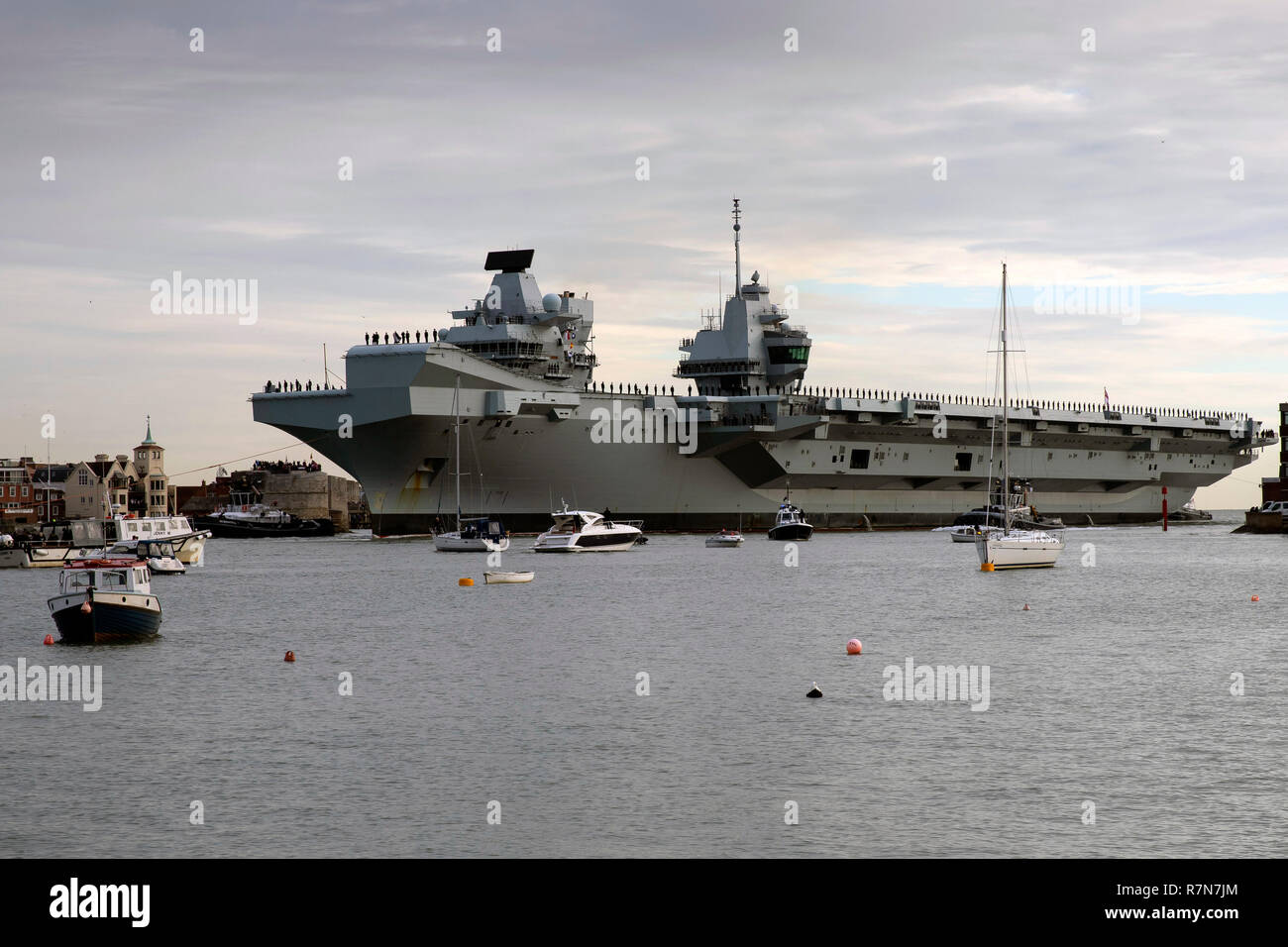 Royal Navy flagship HMS Queen Elizabeth arriving at her home port of Portsmouth on 10 December 2018. The Round Tower is to the left of the image - Stock Image