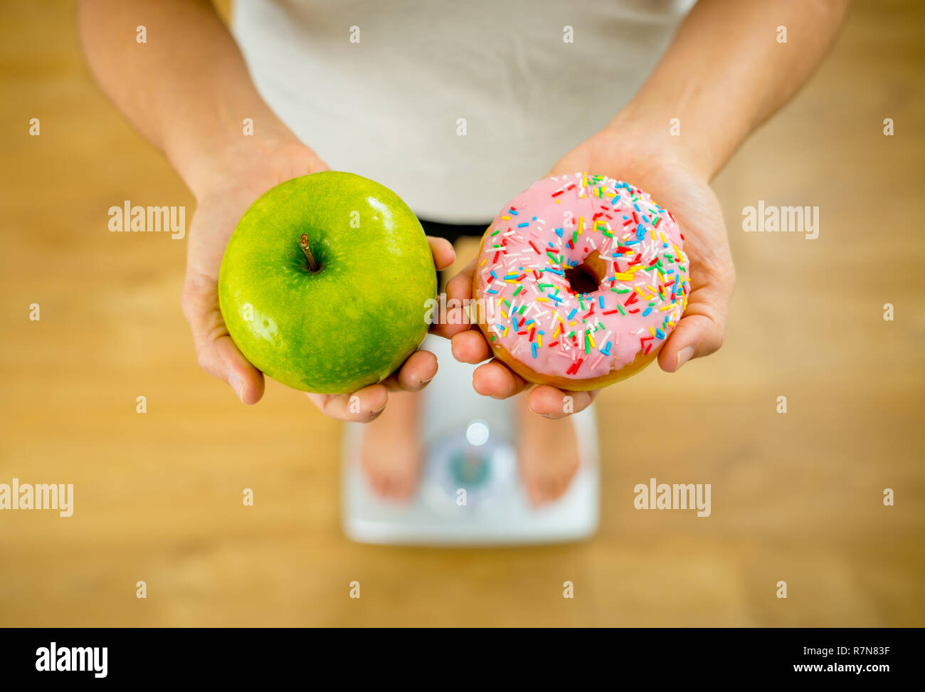 Close up of woman on scale holding on hands apple and doughnut making choice between healthy unhealthy food dessert while measuring body weight in Nut - Stock Image