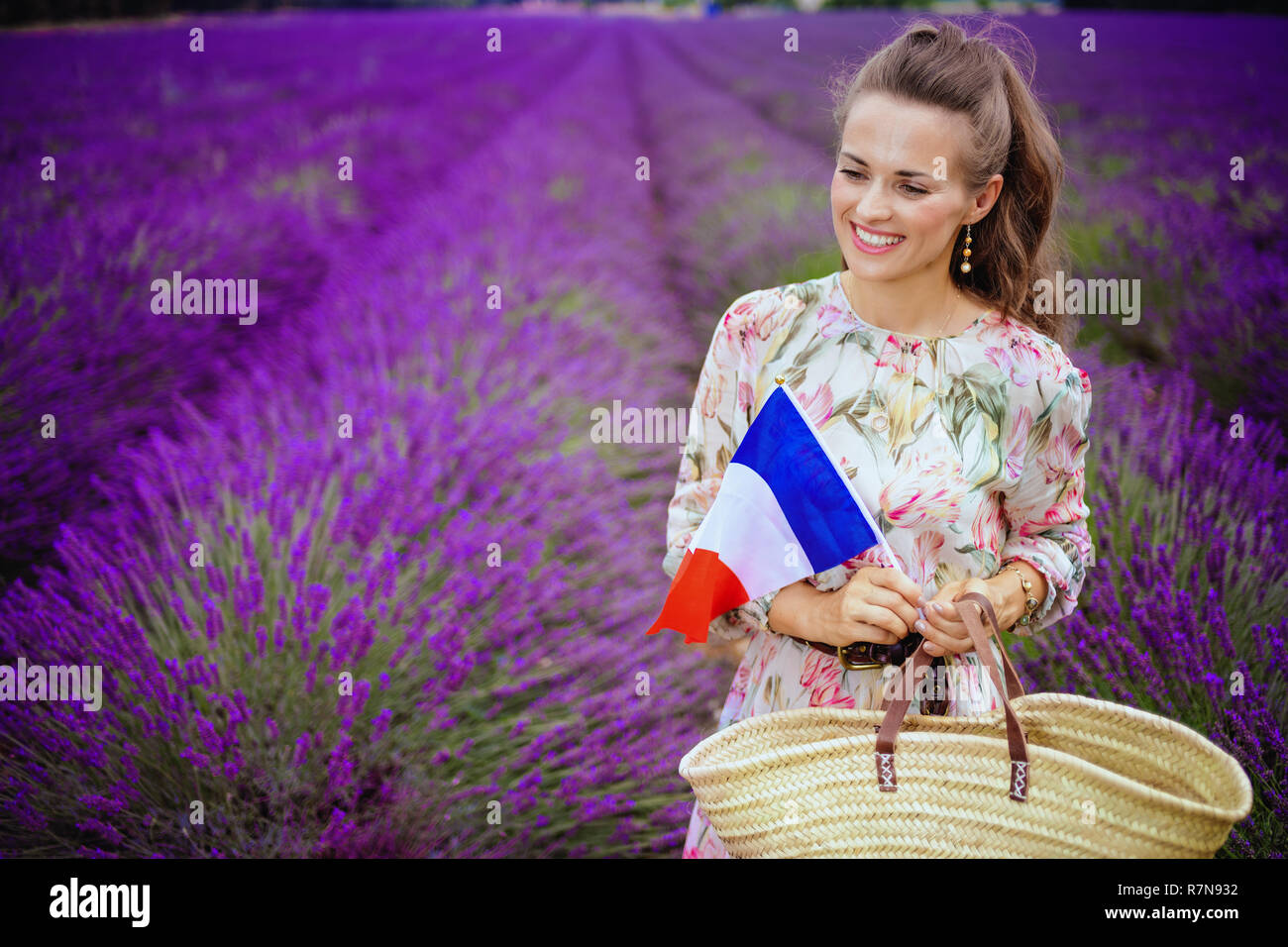 happy elegant woman in floral dress with straw bag and French flag against lavender field of Provence, France. The dream came true! Tourist woman enjo Stock Photo