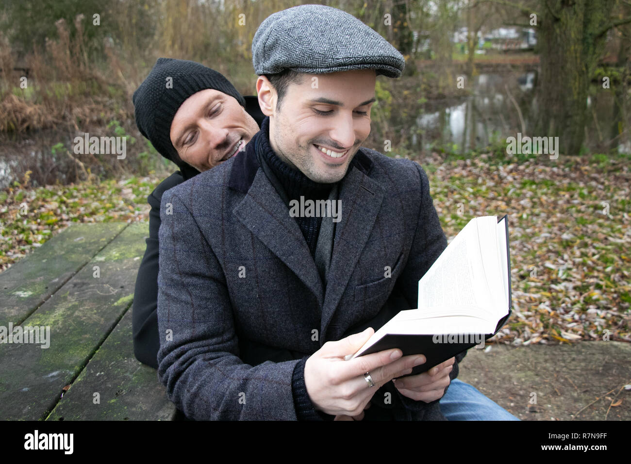 Male gay husbands sit on park bench to read to each other from book - Stock Image