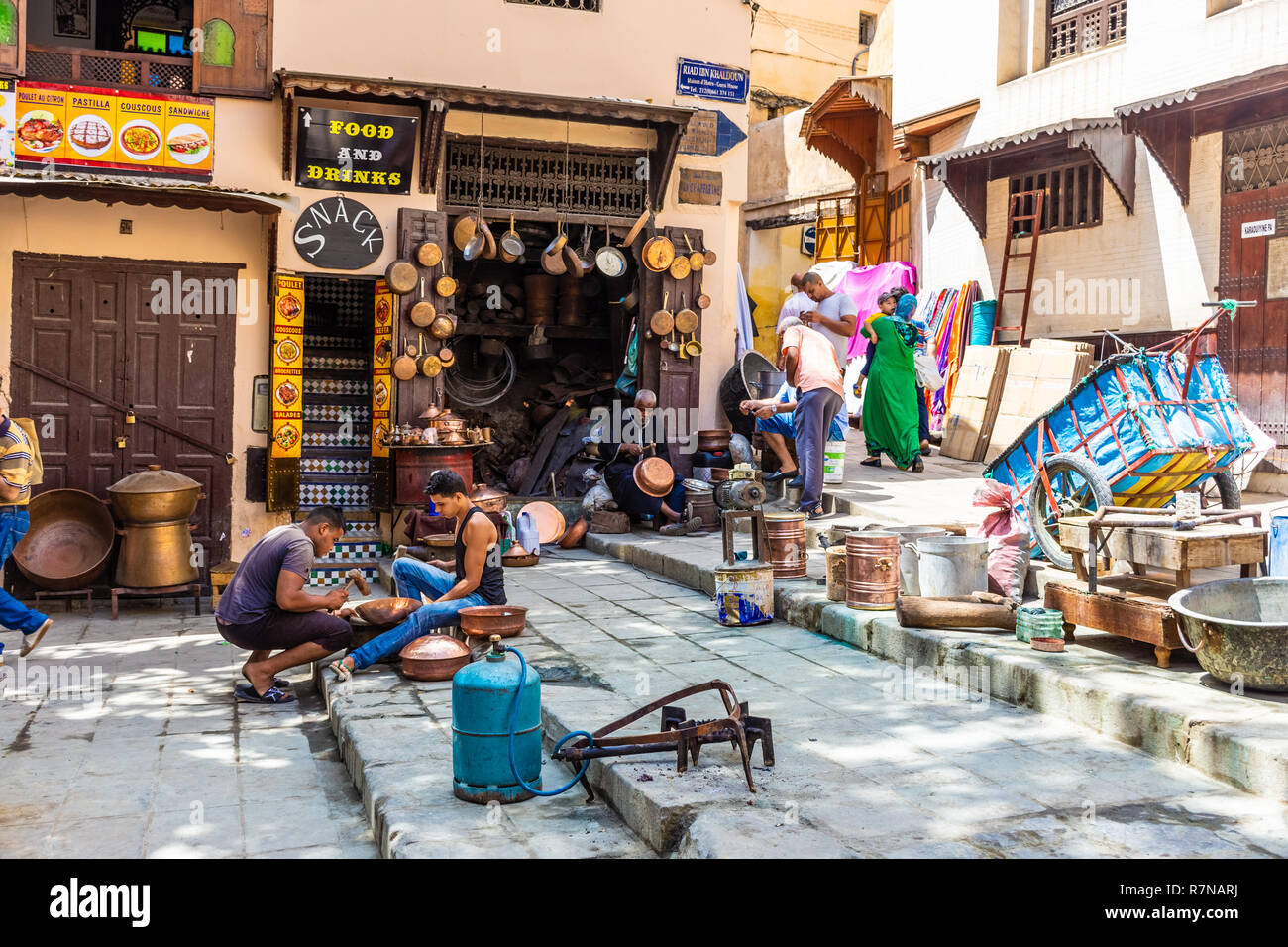 FEZ, MOROCCO, 15 AUGUST 2018: People in their traditional activity of crafting with copper in the medina - Stock Image