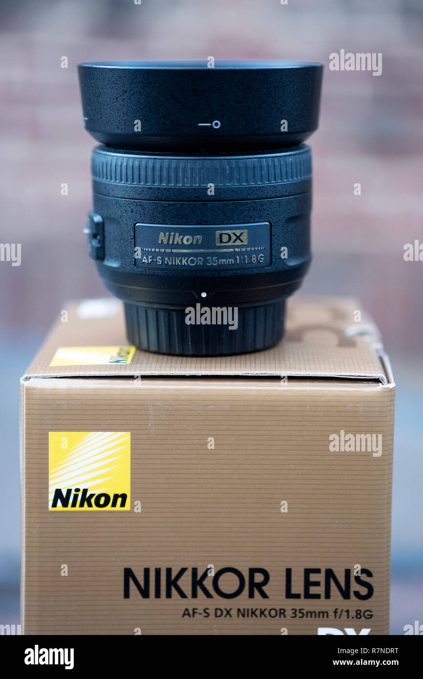 A 35mm Nikon Lens on top of the box that it came in. - Stock Image