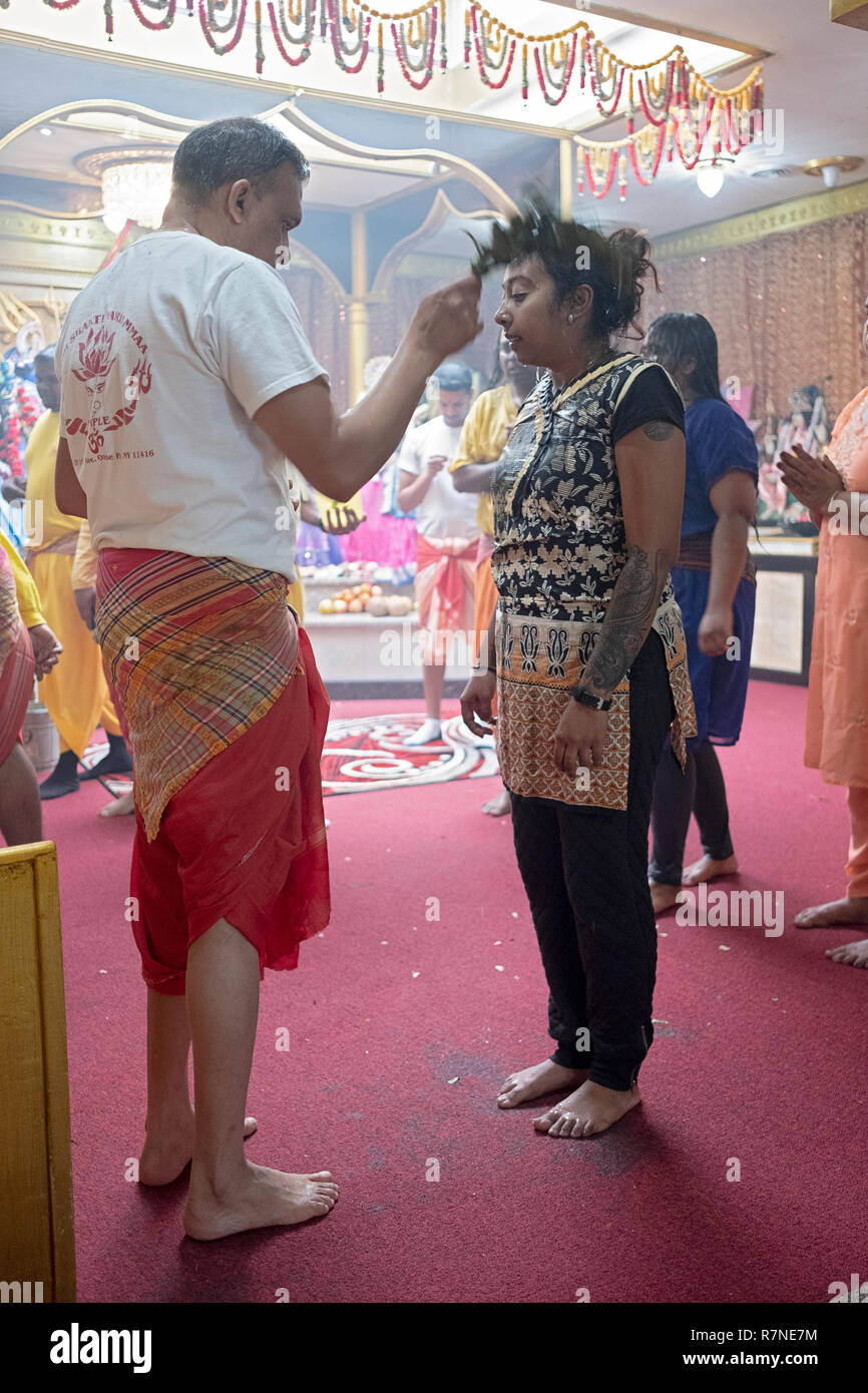 A young lady gets a blessing and cleansing at a Hindu temple in New York City. - Stock Image