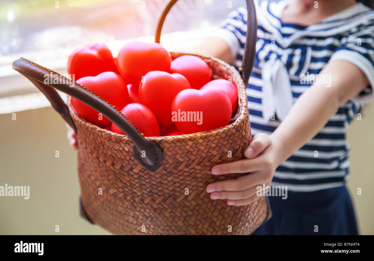 girl in navy blue striped dress handing basket of red hearts represents helping hands, family support, morale, purity, innocence, cheer up, loves, hos - Stock Image