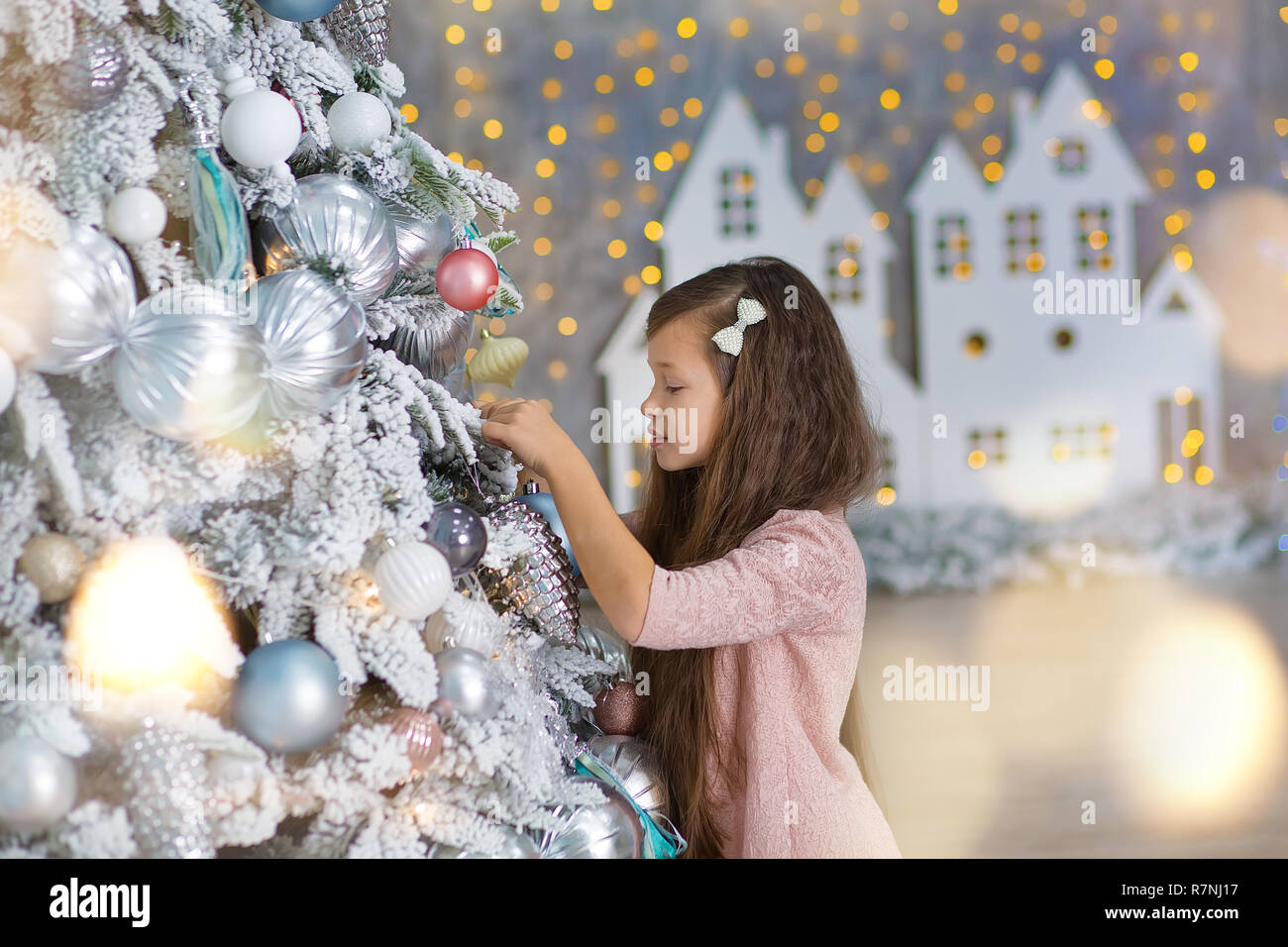 Cute girl near the Christmas tree enjoy miracle winter time. Christmas concept. Belief in miracles - Stock Image