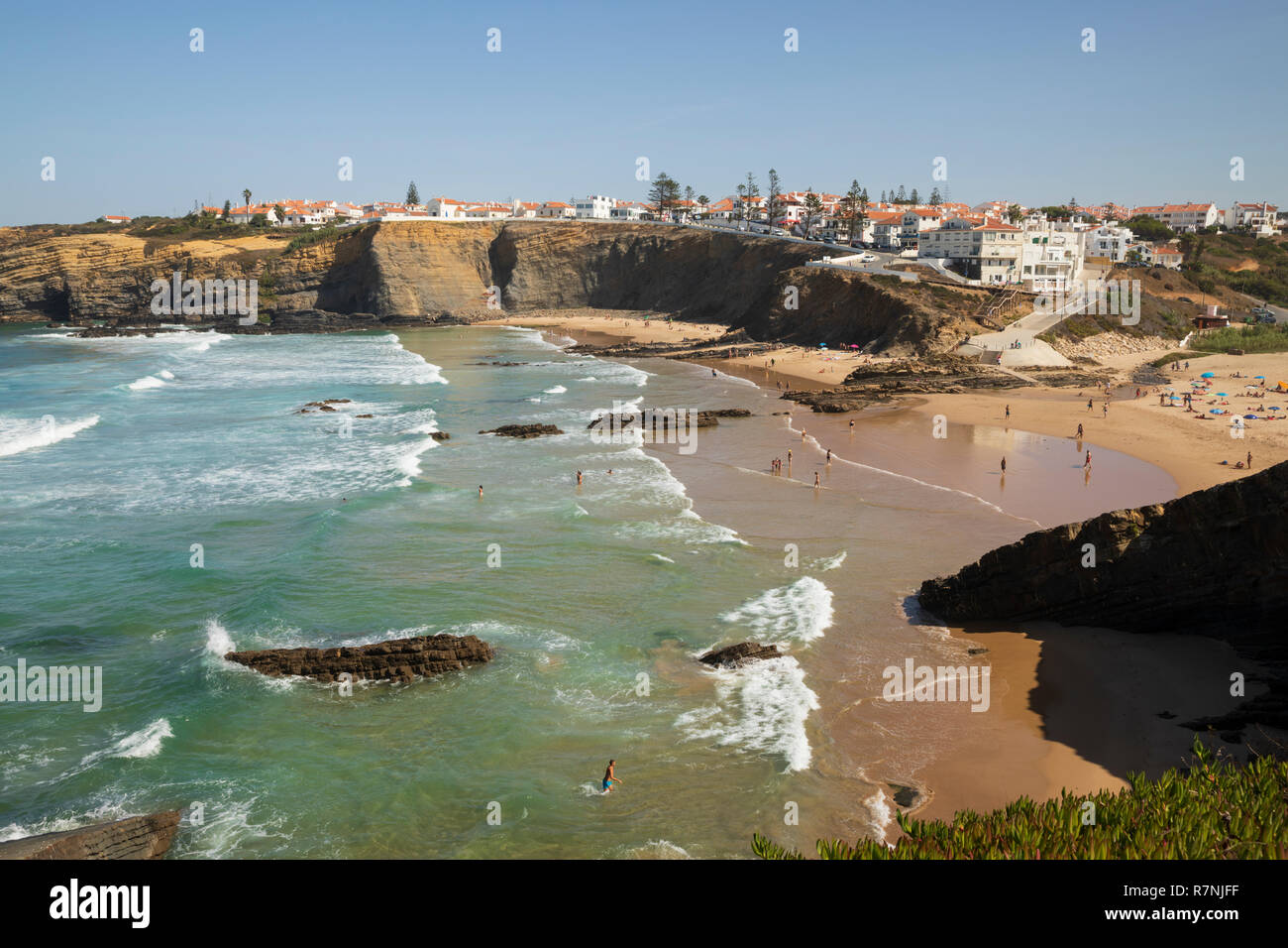 Whitewashed town on cliffs above beach and breaking waves of the Atlantic sea in noon sun, Zambujeira do Mar, Alentejo region, Portugal, Europe - Stock Image