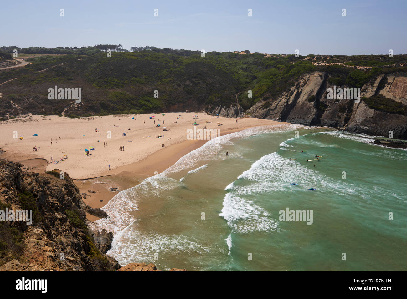Praia do Carvalhal with breaking Atlantic waves in the afternoon sun, Zambujeira do Mar, Alentejo region, Portugal, Europe - Stock Image