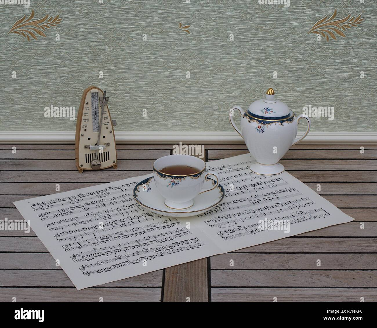 English teacup with saucer and sugar bowl, fine bone china porcelain, and a metronome for music on a sheet of music - Stock Image