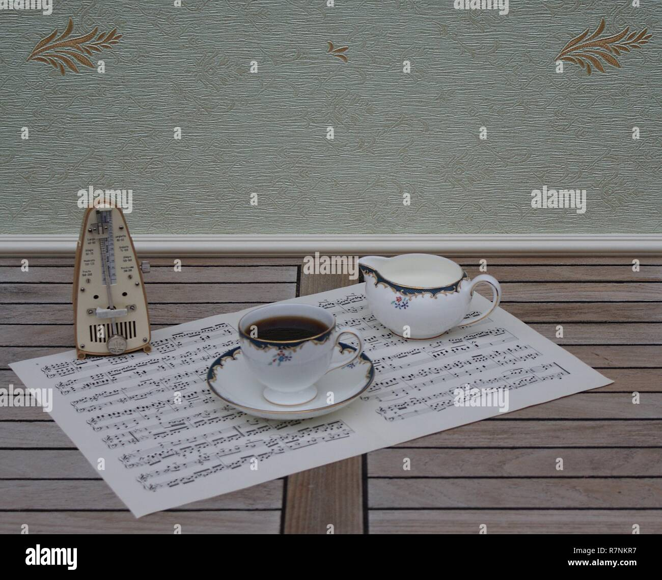 English teacup with saucer and cream jug, fine bone china porcelain, and a metronome for music on a sheet of music - Stock Image