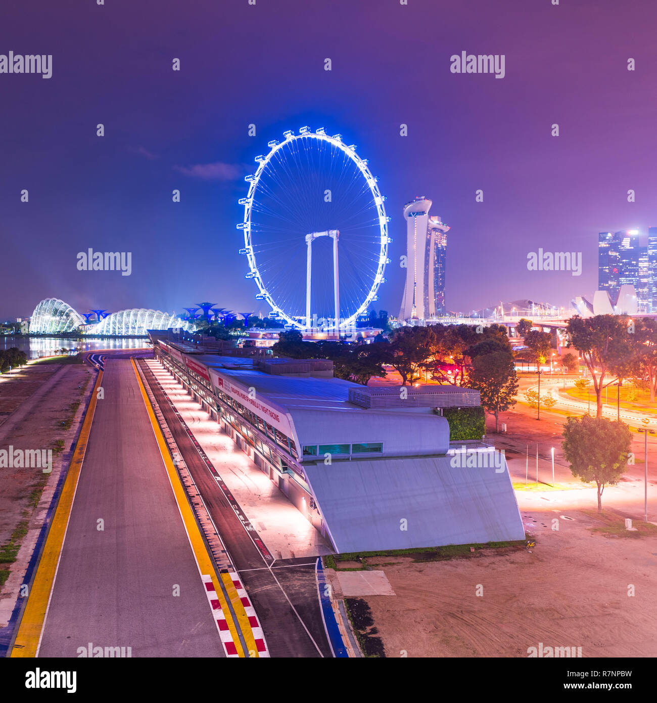 Singapore, 31 Oct 2018: a night viesw of the Formula One Singapore Grand Prix circuit stands in front of the Marina Bay area and the Flyer Wheel. Stock Photo