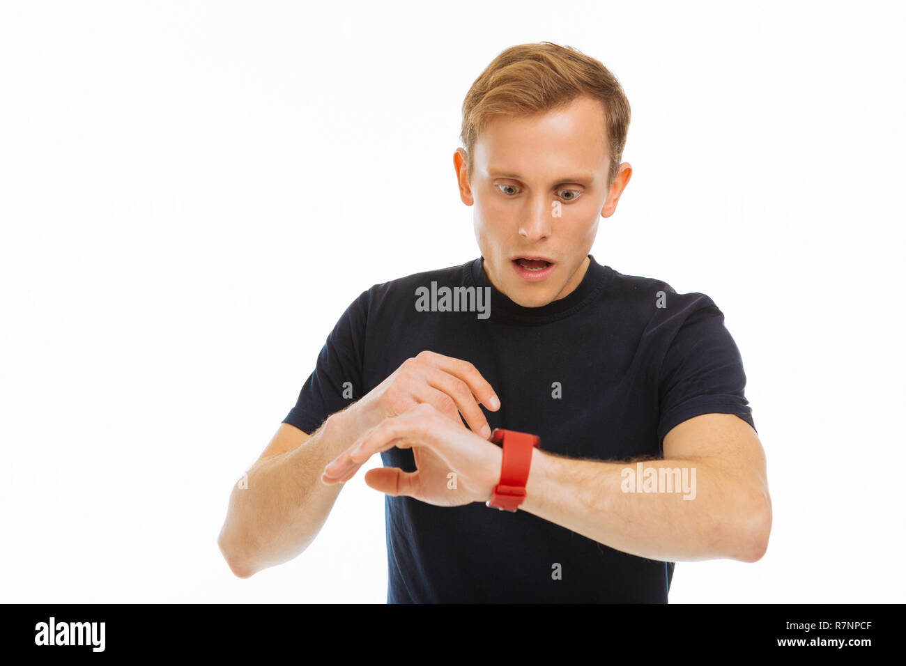 Nice blonde man checking the time on his watch - Stock Image