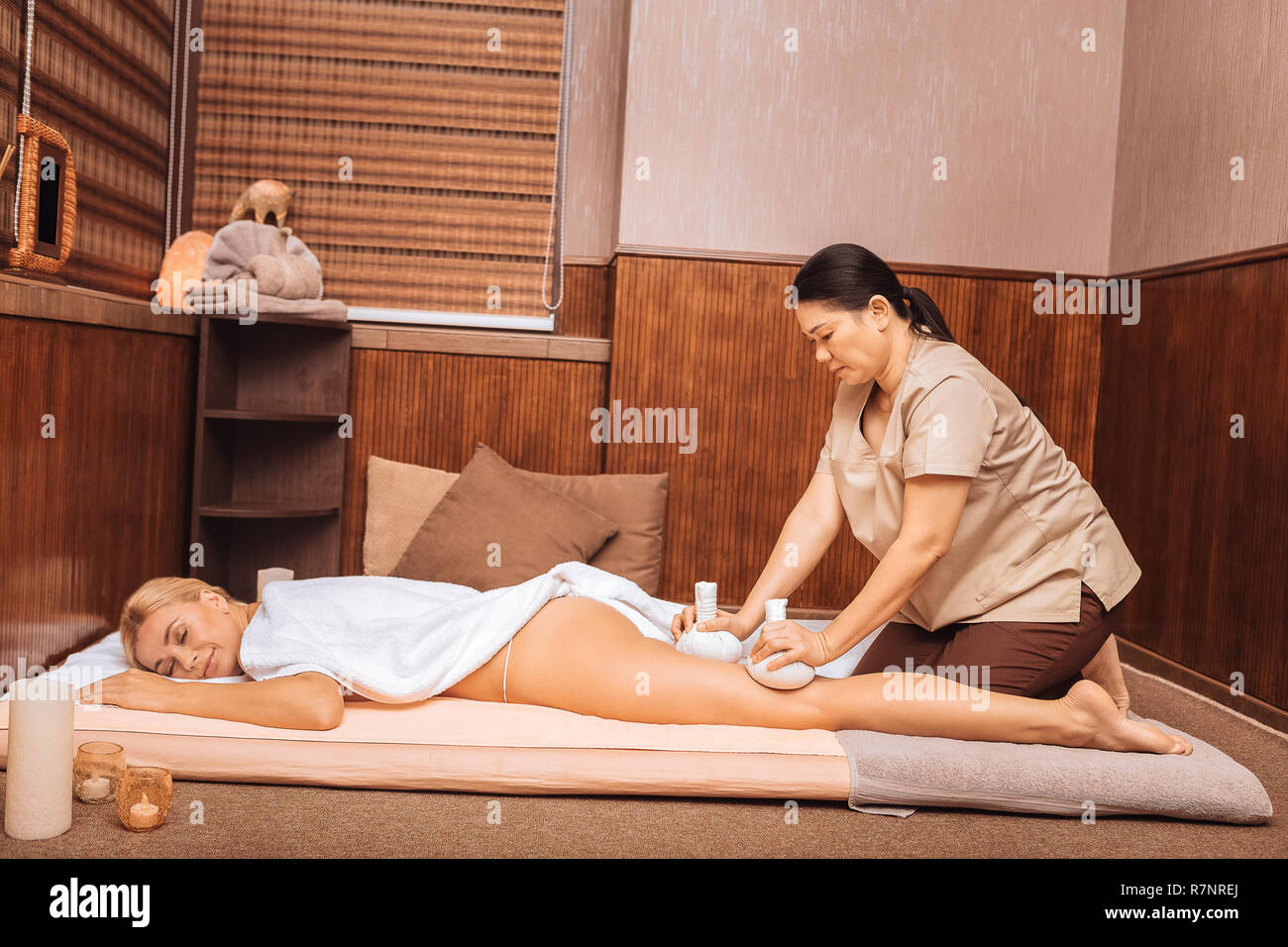Nice skilled masseuse massaging her clients body Stock Photo