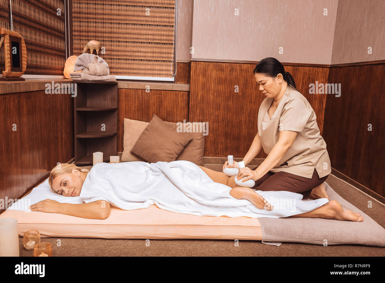 Nice relaxed woman enjoying the massage with bags Stock Photo