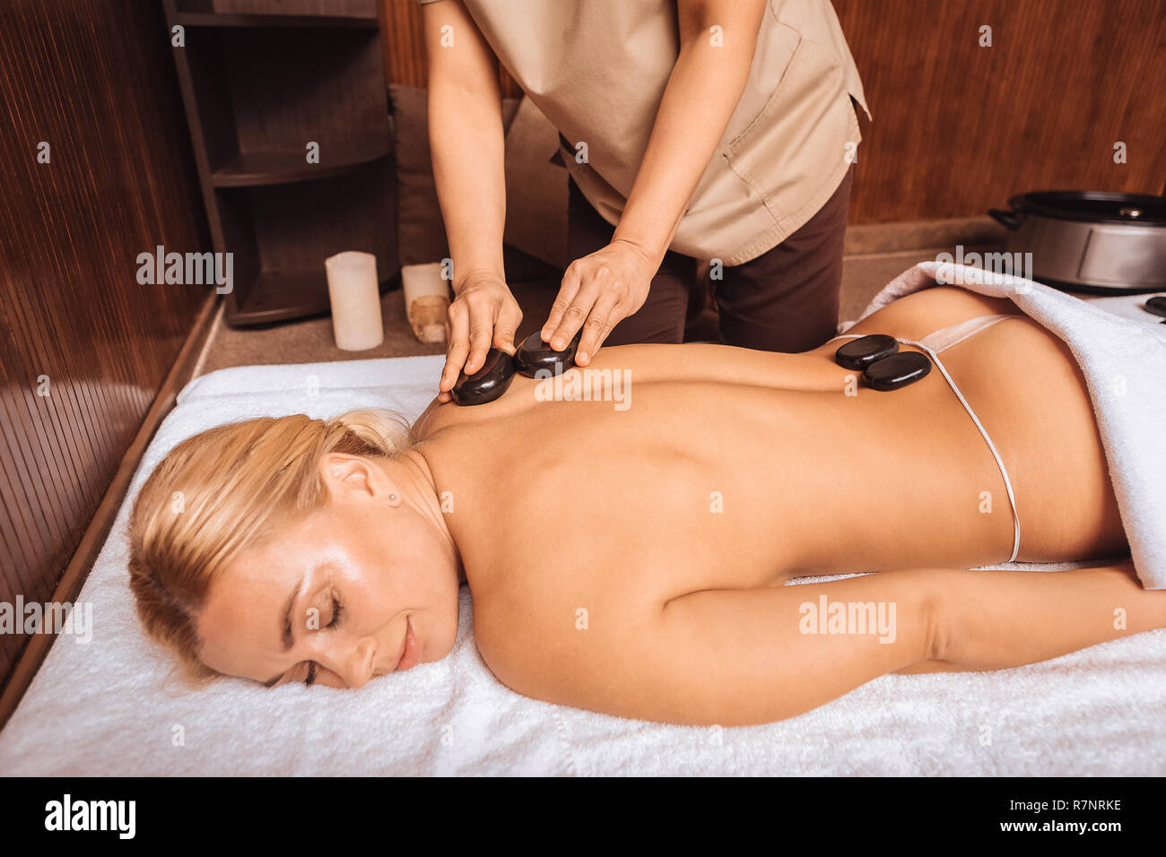 Nice pleasant woman lying with hot stones on her body Stock Photo