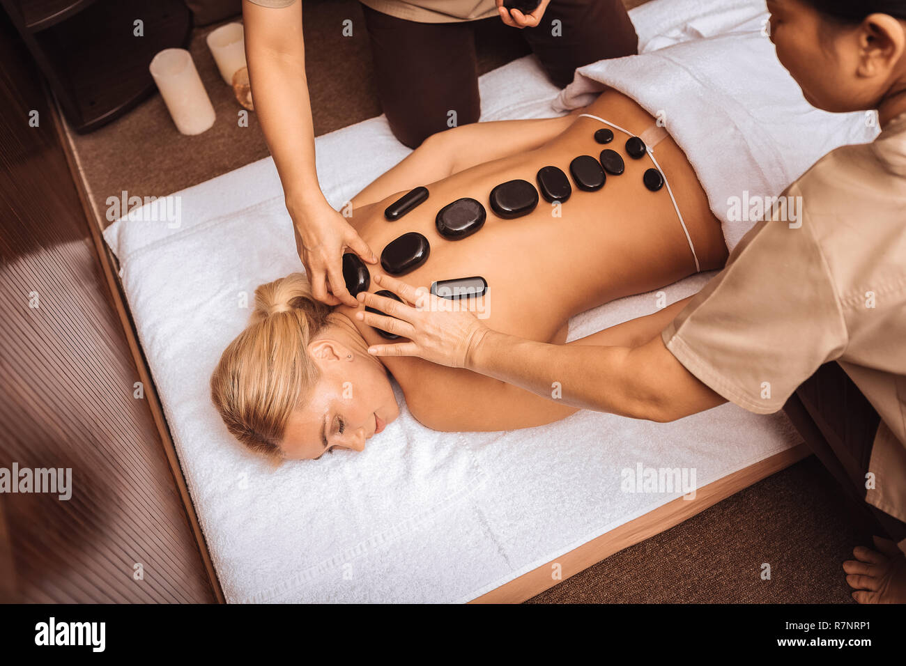 Professional Asian masseuses putting hot stones on female back Stock Photo