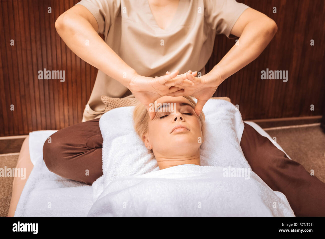 Nice professional female masseuse massaging the temples Stock Photo