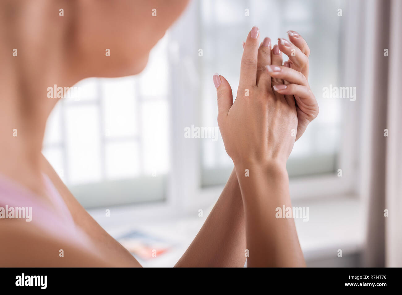 Beautiful woman with sensitive skin putting some cream on her hands - Stock Image