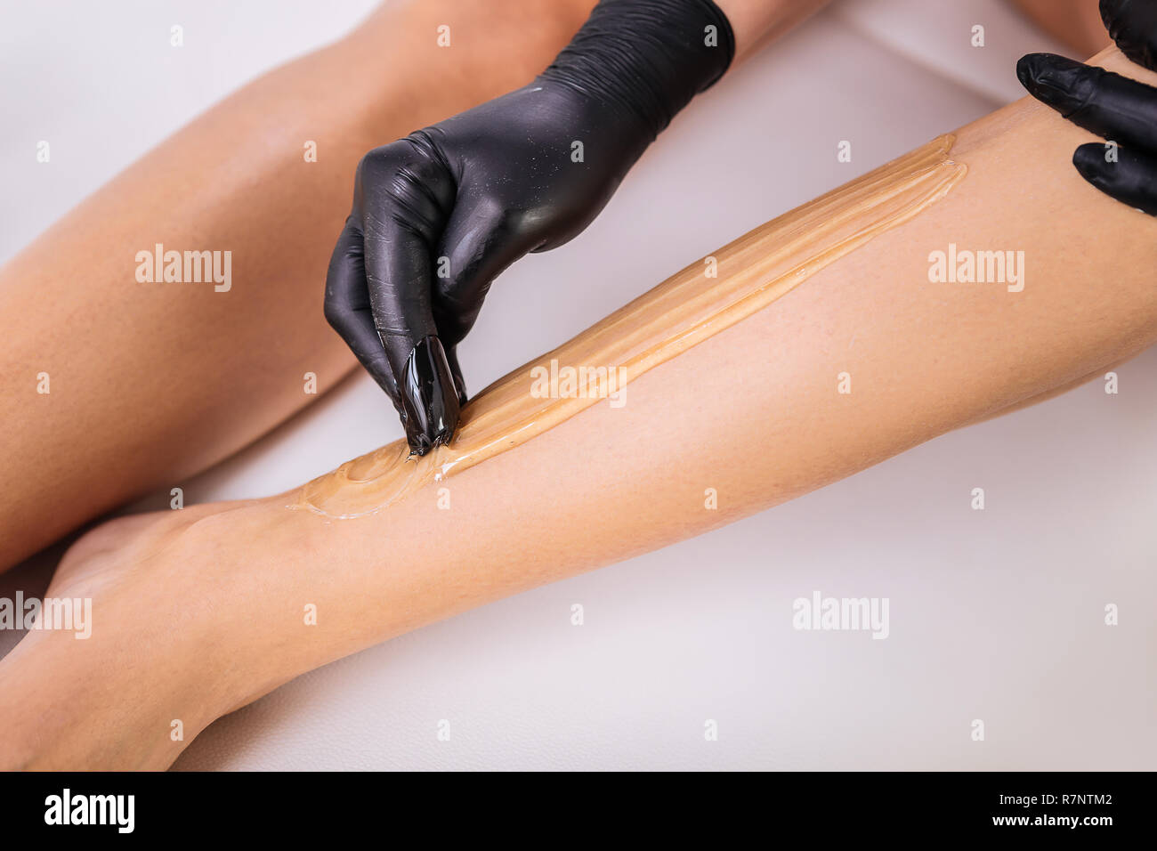 Master in hair removal making sugaring for her client lying on bed Stock Photo
