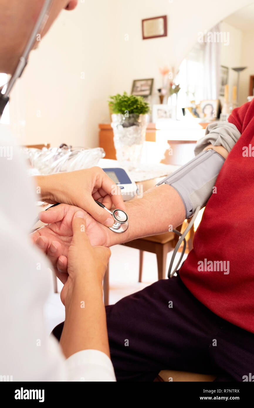 closeup of a caucasian doctor man, in a white coat, measuring the blood pressure of a senior caucasian patient man with a sphygmomanometer, at his hom - Stock Image