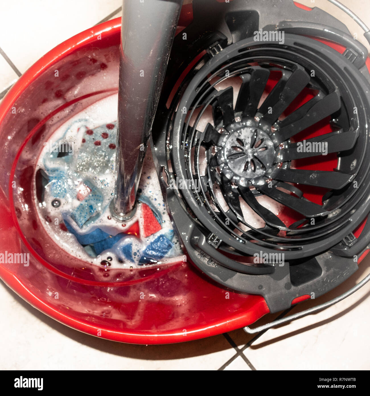 A mop and bucket used by professional cleaners in a kitchen - Stock Image