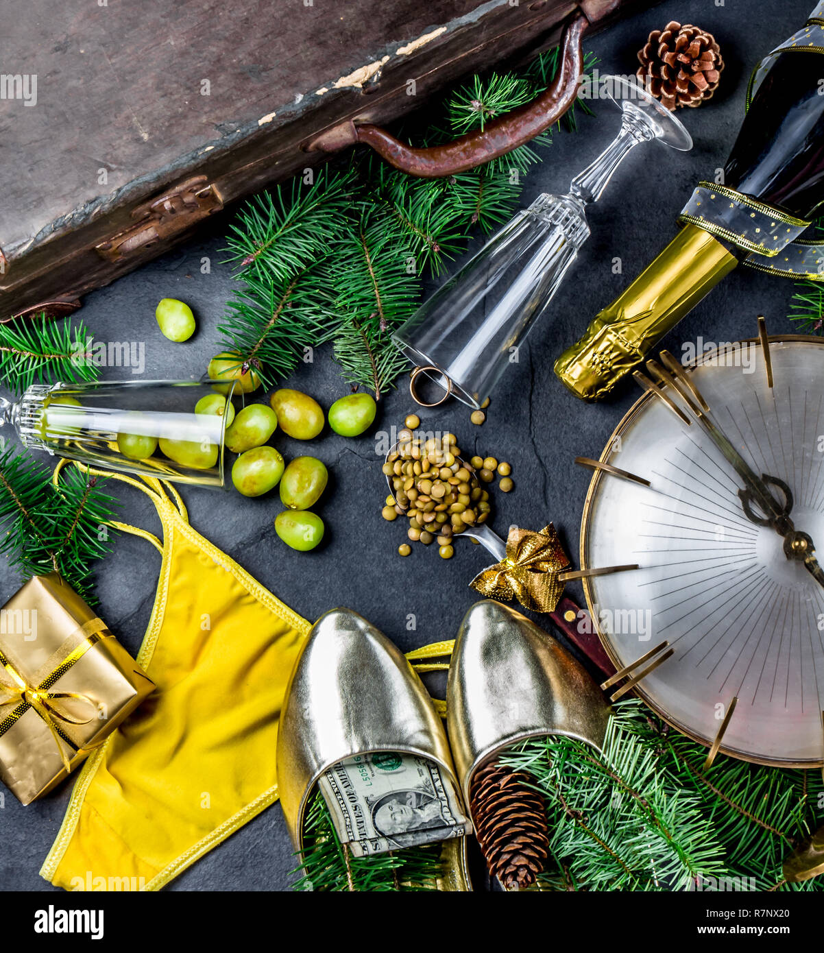 LATIN AMERICAN AND SPANISH NEW YEAR TRADITIONS. empty suitcase, lentil spoon, yellow interior clothes, gold ring in champagne, 12 grapes, money in shoe. Christmas background - Stock Image