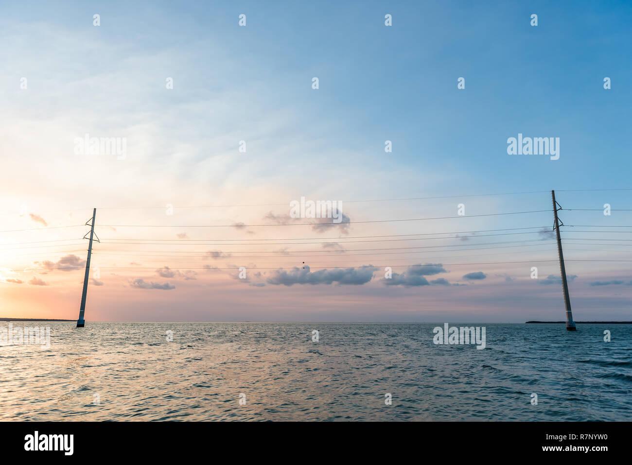 Sunset in Islamorada, Florida Keys, with orange blue dreamy pink pastel sky, power lines, water on gulf of Mexico, or Atlantic Ocean, horizon Stock Photo