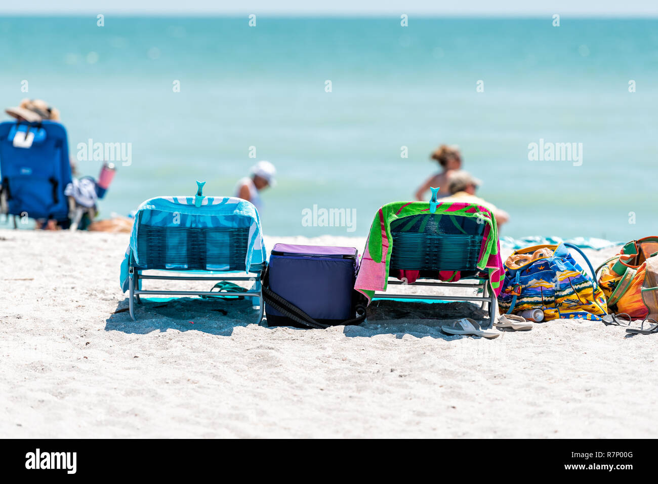 Sanibel Island, USA - April 29, 2018: Bowman's beach with white sand, empty beach chairs, colorful towels, slippers, flip flops, people walking in bac Stock Photo