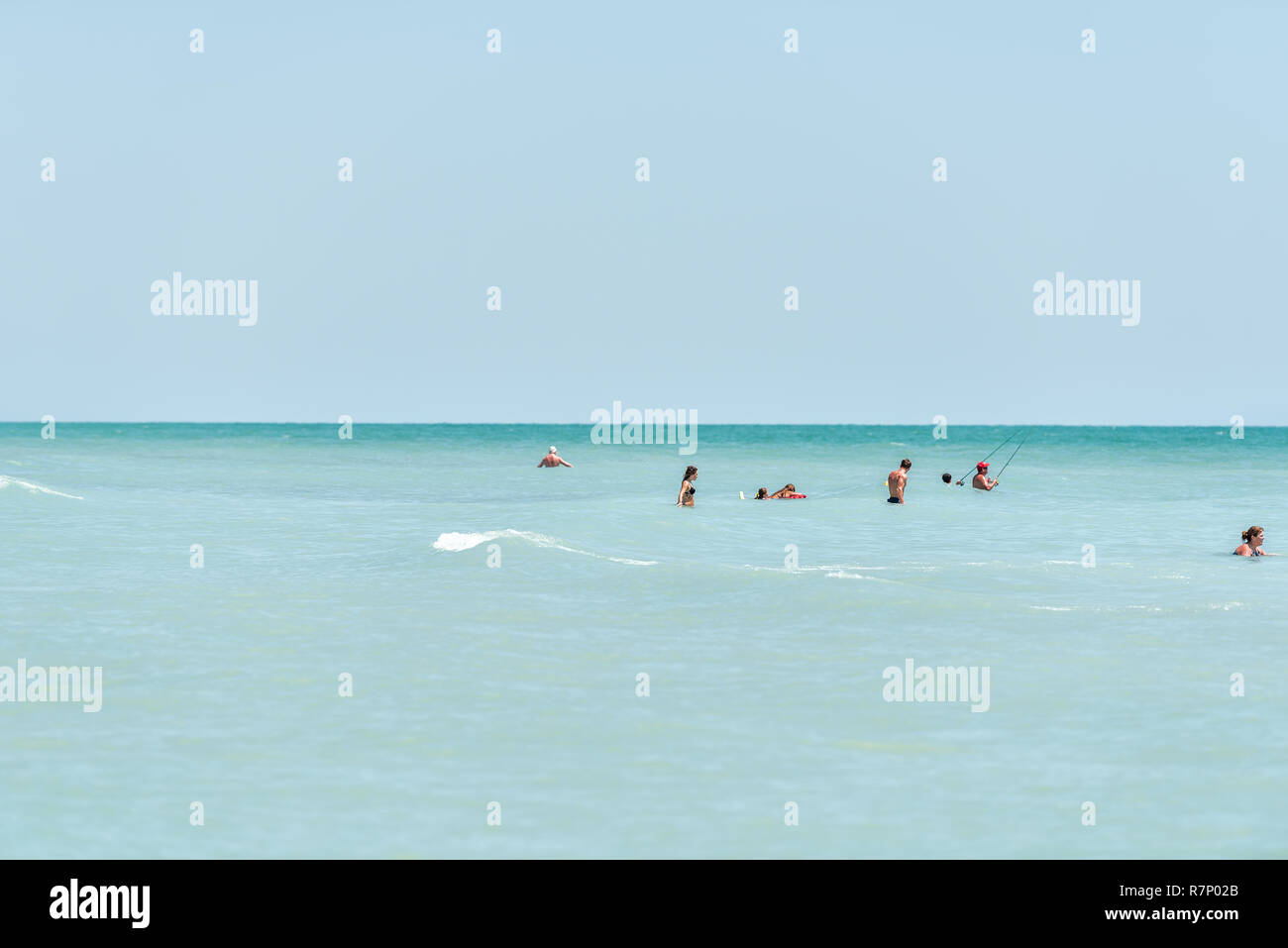 Sanibel Island, USA - April 29, 2018: Bowman's beach, Florida with many people swimming standing on shore in turquoise water on sunny day, fishing Stock Photo