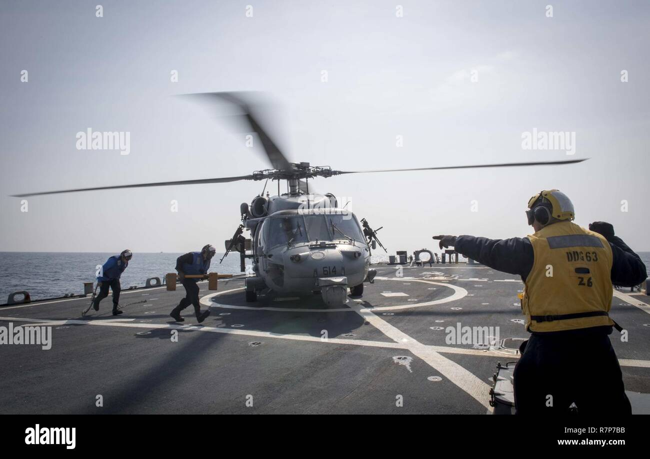 WATERS EAST OF THE KOREAN PENINSULA (March 22, 2017) Boatswains Mate 2nd Class Javier Garza, assigned to the Arleigh Burke-class guided-missile destroyer USS Stethem (DDG 63), gives the signal to secure a MH-60 helicopter during a passenger transport with the Nimitz-class aircraft carrier USS Carl Vinson (CVN 70) during Foal Eagle (FE) 17. FE 17 is a series of annual training events designed to increase readiness to defend the ROK, protect the region, and maintain stability in the Korean Peninsula. - Stock Image