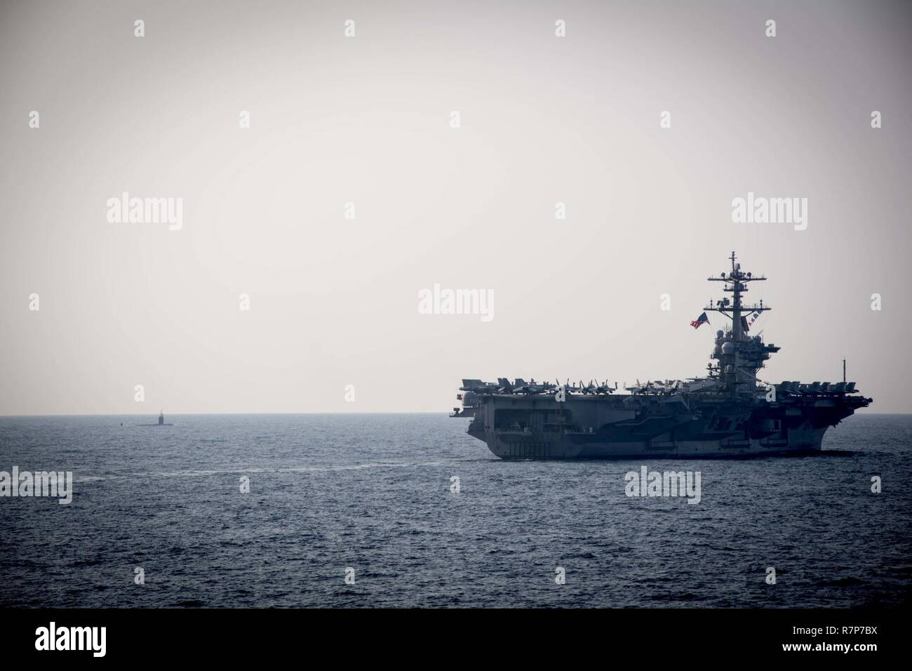 WATERS EAST OF THE KOREAN PENINSULA (March 22, 2017) The Nimitz-class aircraft carrier USS Carl Vinson (CVN 70) and blanksubmarine steam ahead of the Arleigh Burke-class guided-missile destroyer USS Stethem (DDG 63) during a surface maenuvers exercise with several other U.S. and Republic of Korea Navy ships and submarines during Foal Eagle (FE) 17. FE 17 is a series of annual training events designed to increase readiness to defend the ROK, protect the region, and maintain stability in the Korean Peninsula. - Stock Image