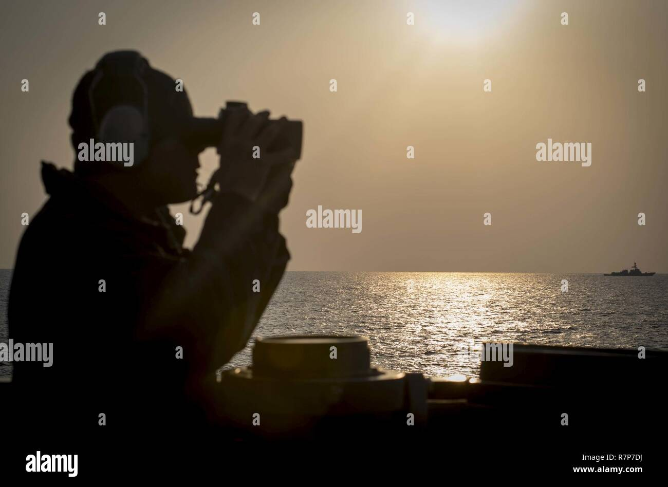 WATERS EAST OF THE KOREAN PENINSULA (March 22, 2017) Seaman Nathaniel Irish, assigned to the Arleigh Burke-class guided-missile destroyer USS Stethem (DDG 63), scans the horizon as the ship participates in surface maneuvers with USS Wayne E. Meyer (DDG 108) and several other U.S. and Republic of Korea Navy ships and submarines during Foal Eagle (FE) 17. FE 17 is a series of annual training events designed to increase readiness to defend the ROK, protect the region, and maintain stability in the Korean Peninsula. - Stock Image