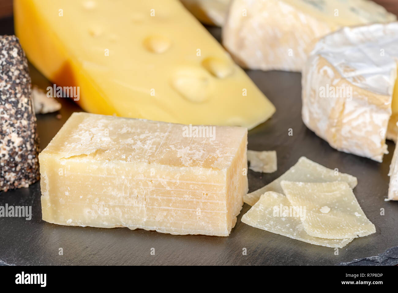 portion and slaced of fresh parmesan cheese and various types of cheese on black slate, close up - Stock Image