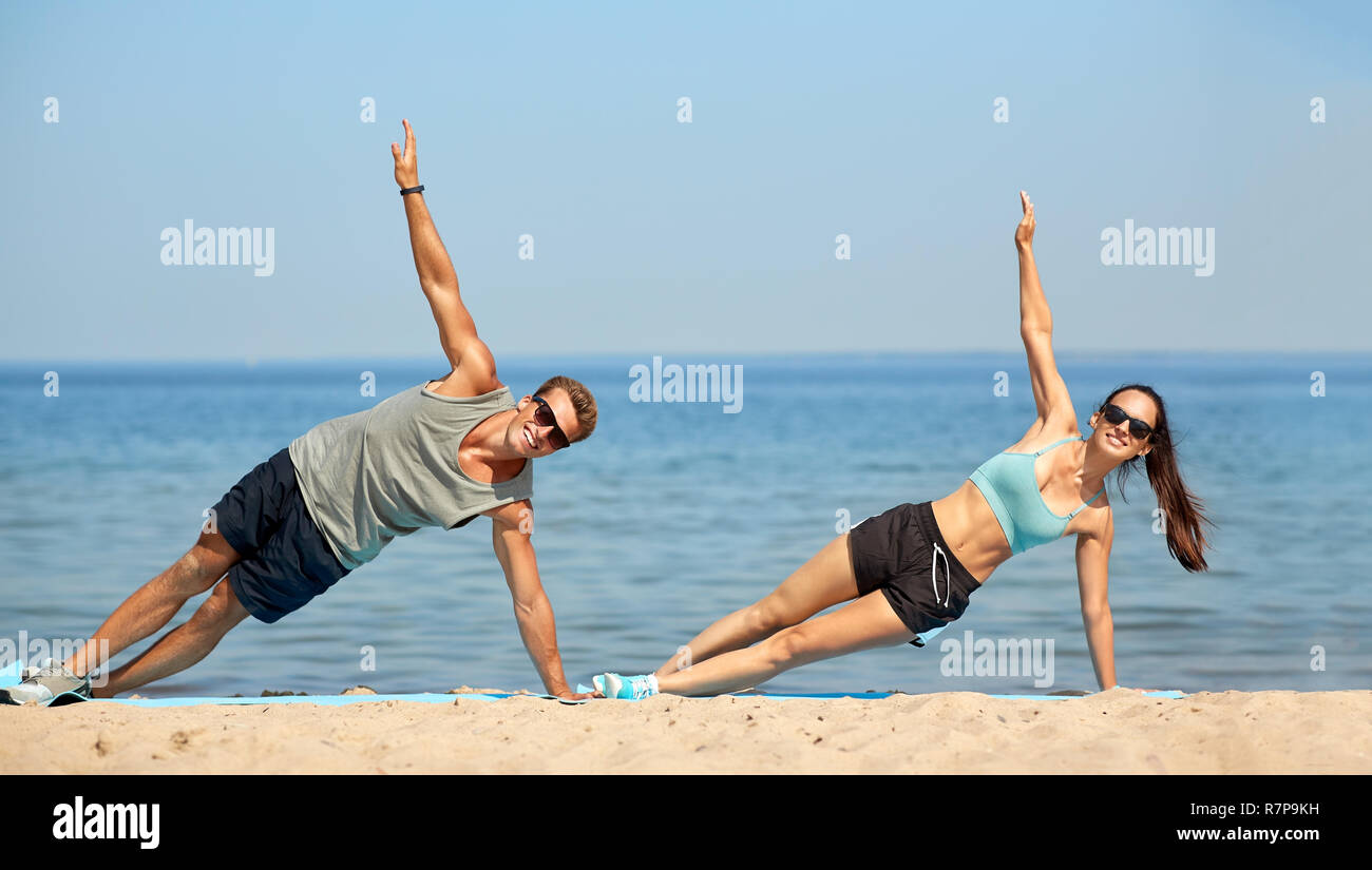 couple doing side plank exercise on summer beach Stock Photo