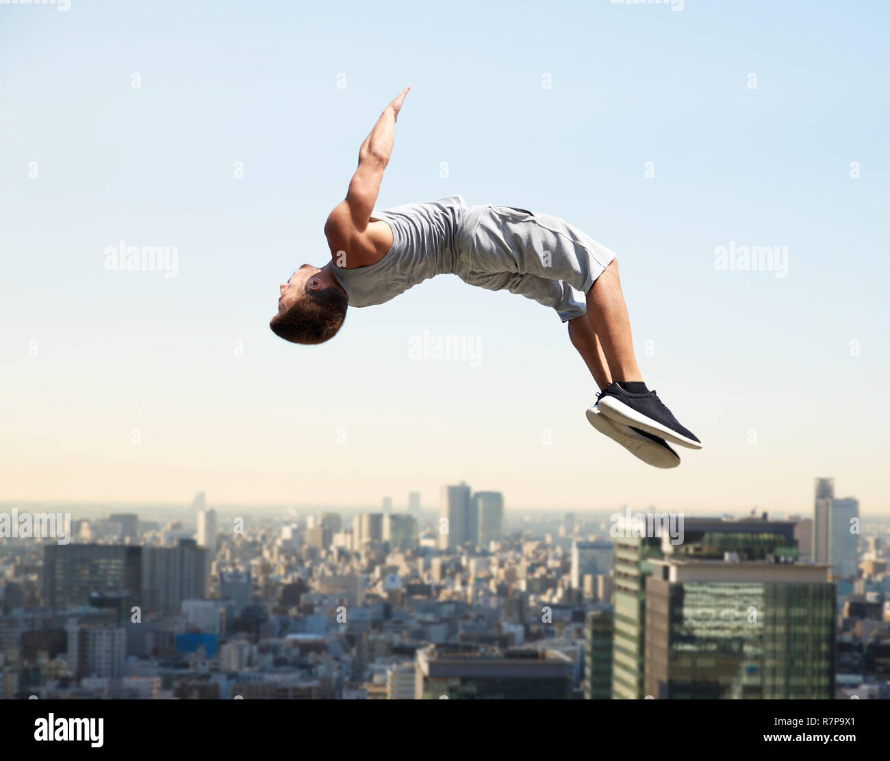 man making parkour jumping over tokyo city Stock Photo