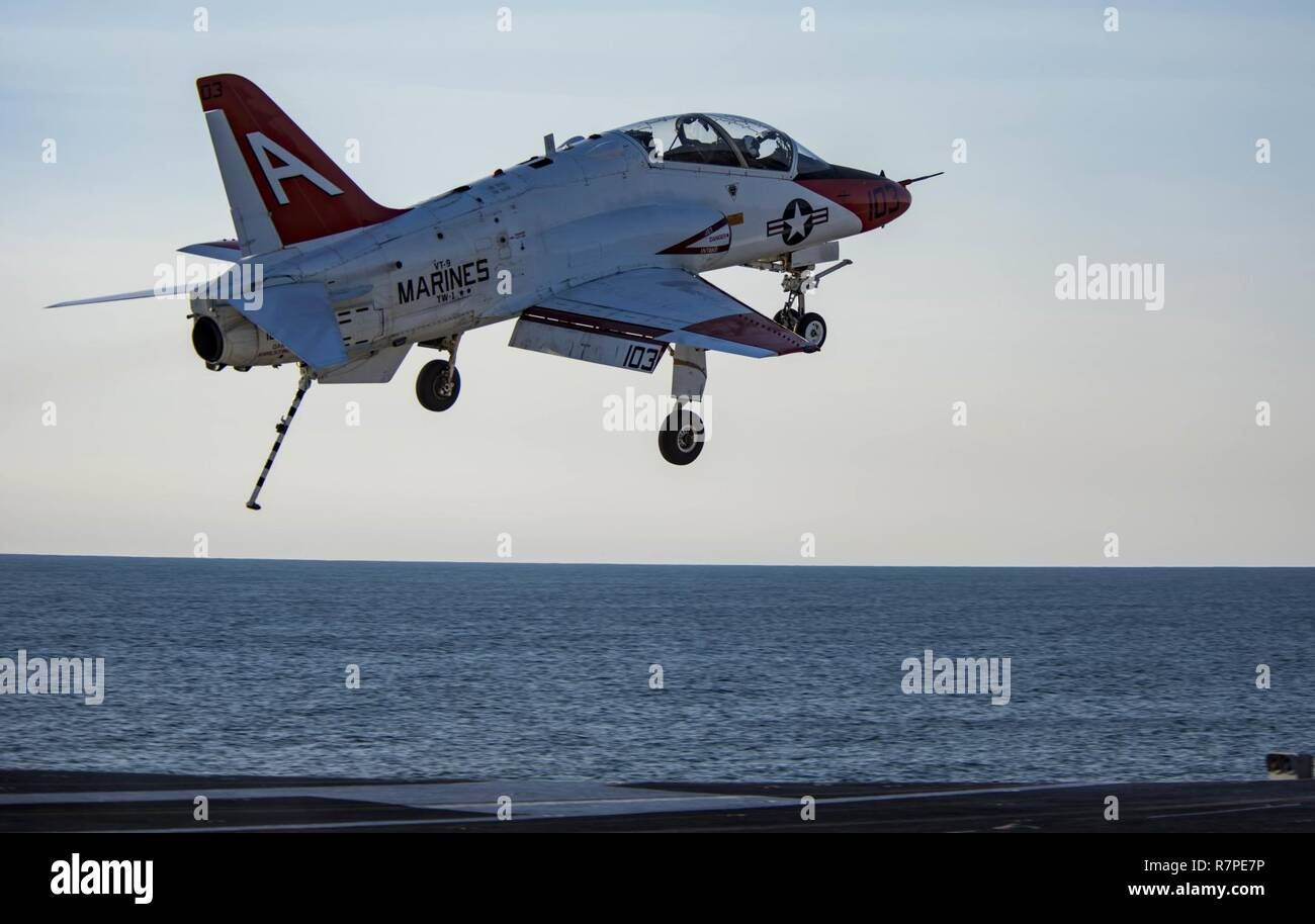 ATLANTIC OCEAN (March 20, 2017) A T-45C Goshawk assigned to Carrier Training Wing (CTW) 1 flies over the flight deck of the aircraft carrier USS Dwight D. Eisenhower (CVN 69) (Ike). Ike is currently conducting aircraft carrier qualifications during the sustainment phase of the Optimized Fleet Response Plan (OFRP). - Stock Image