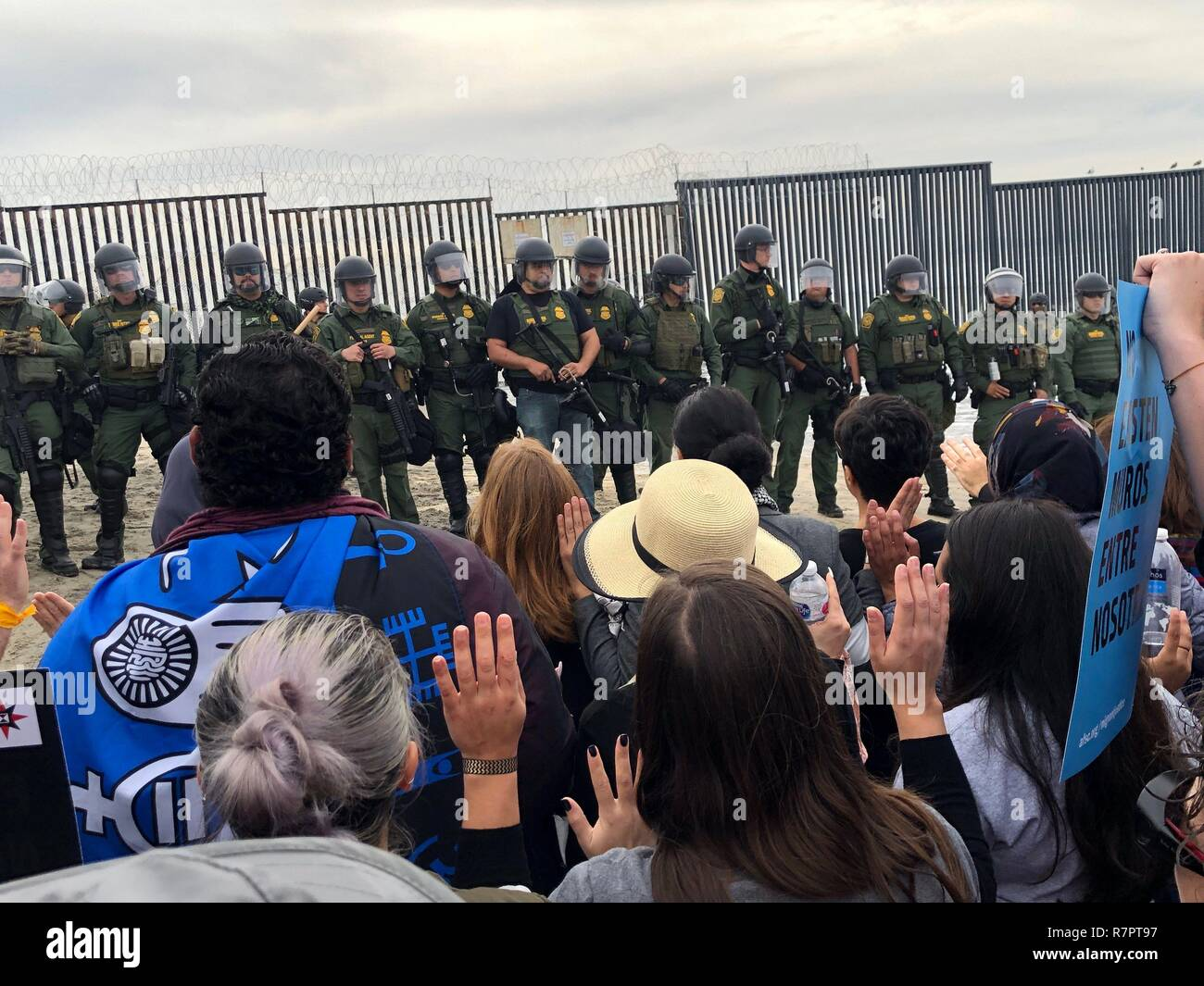 San Diego, United States. 10th Dec, 2018. A group of demonstrators, mostly religious, confronts members of the Federal Protection Service (FPS) during an act of civil disobedience in support of the migrant caravan, near the border wall between Tijuana (Mexico) and San Diego, California, USA, 10 December 2018. More than three dozen people, mostly religious, were arrested today at the border wall between Tijuana (Mexico) and San Diego (California), during an act of support for the immigrant caravan seeking political asylum in United States. Credit: Alexandra Mendoza/EFE/Alamy Live News - Stock Image