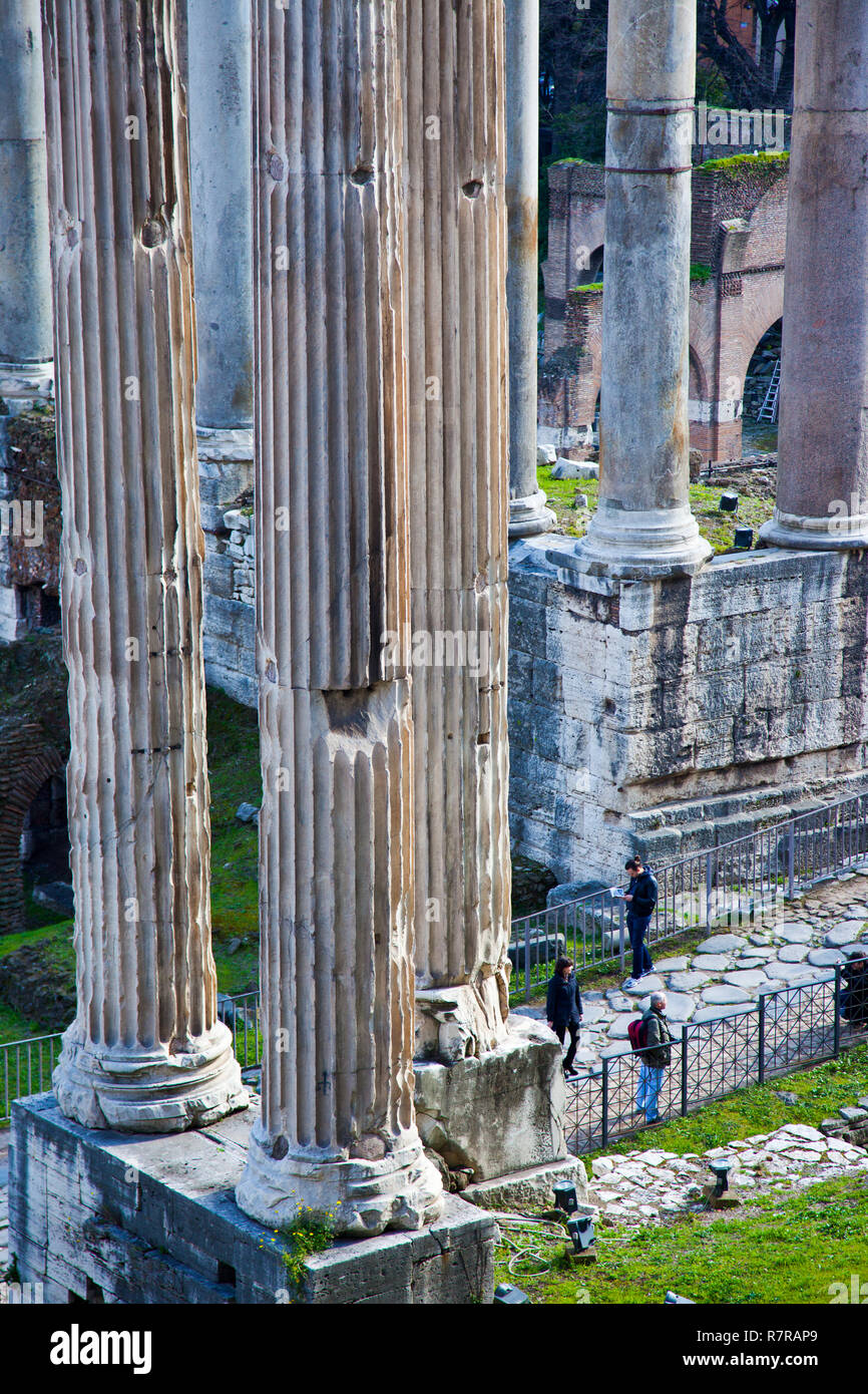 Visitors walk amongst columns at the Roman Forum (Foro Romano) in Rome. - Stock Image