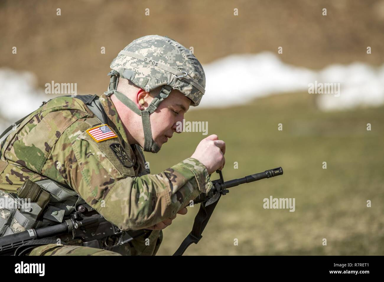 U.S. Army Spc. Mitchell Cooper adjusts his M4's front sights before shooting a weapon qualification during the New York Army National Guard Best Warrior Competition at Camp Smith Training Site March 30, 2017. The Best Warrior competitors represent each of New York's brigades after winning competitions at the company, battalion, and brigade levels. Stock Photo
