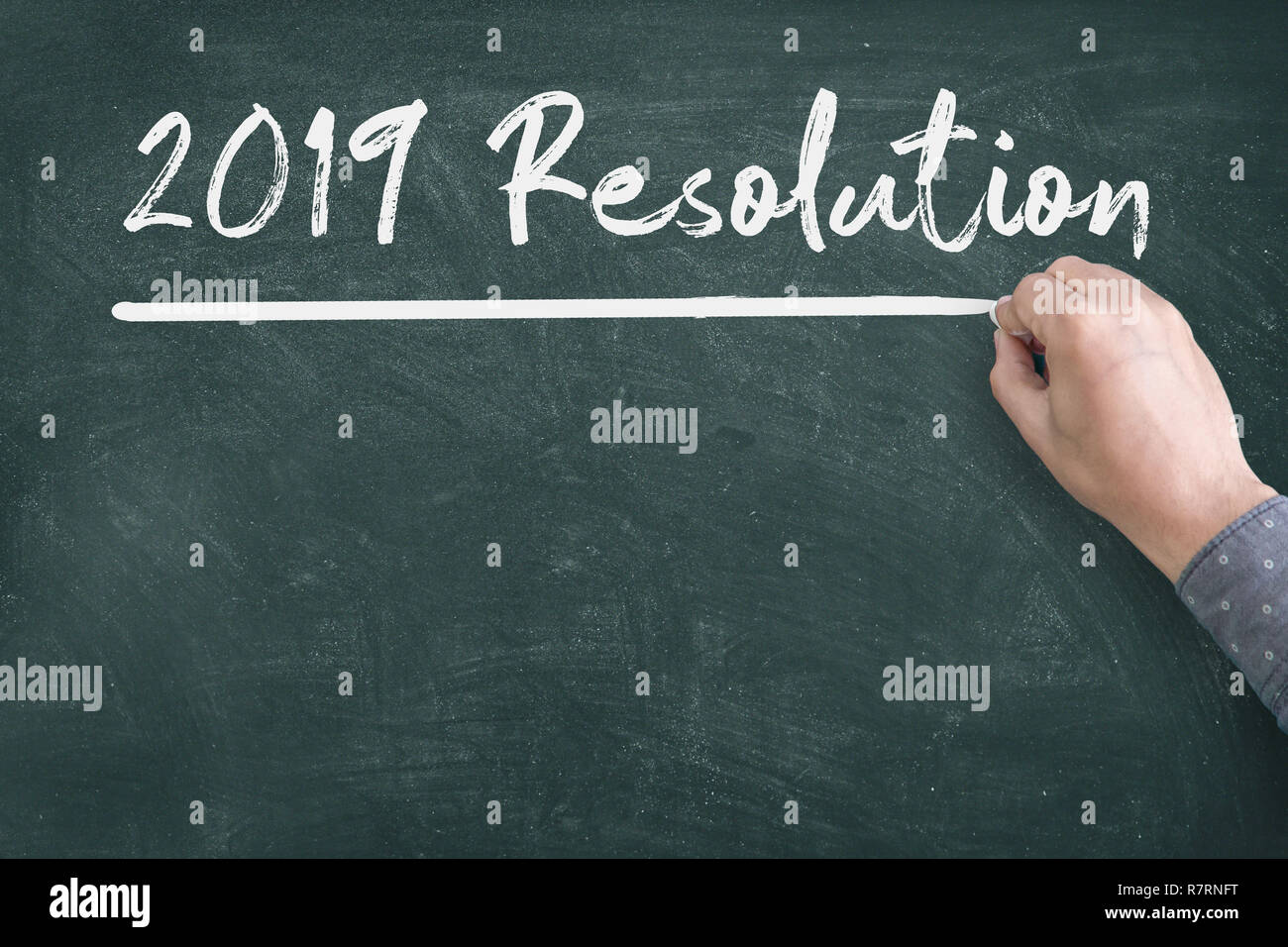Close up of human hand writing 2019 New Year Resolution Check List on Blackboard - Stock Image
