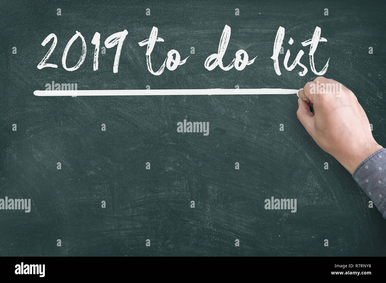 Close up of human hand writing2019 New Year to do List on Blackboard - Stock Image