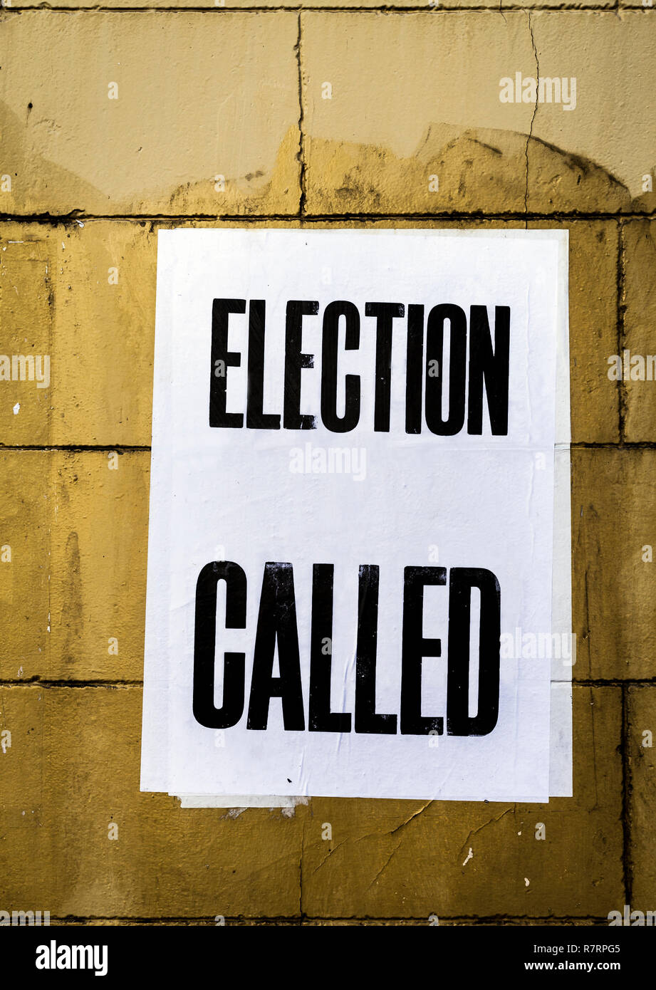Poster with words Election Called in bold text overlapping more poster papers pasted onto dirty stained yellow brick wall. - Stock Image