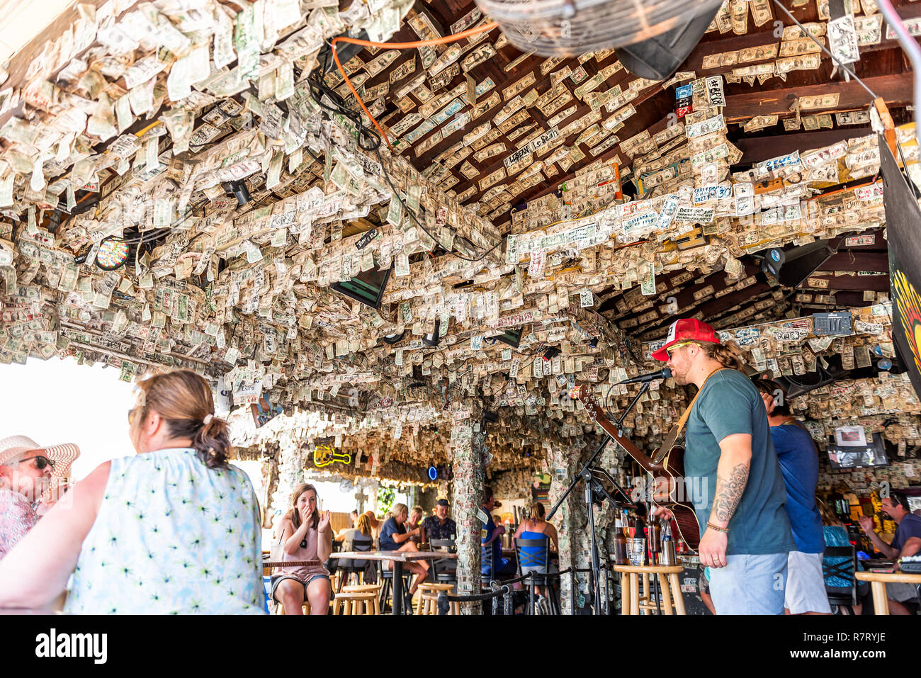 Key West, USA - May 1, 2018: Inside famous Willie T's restaurant bar sign with many dollar bills in Florida, travel, people musicians playing music Stock Photo