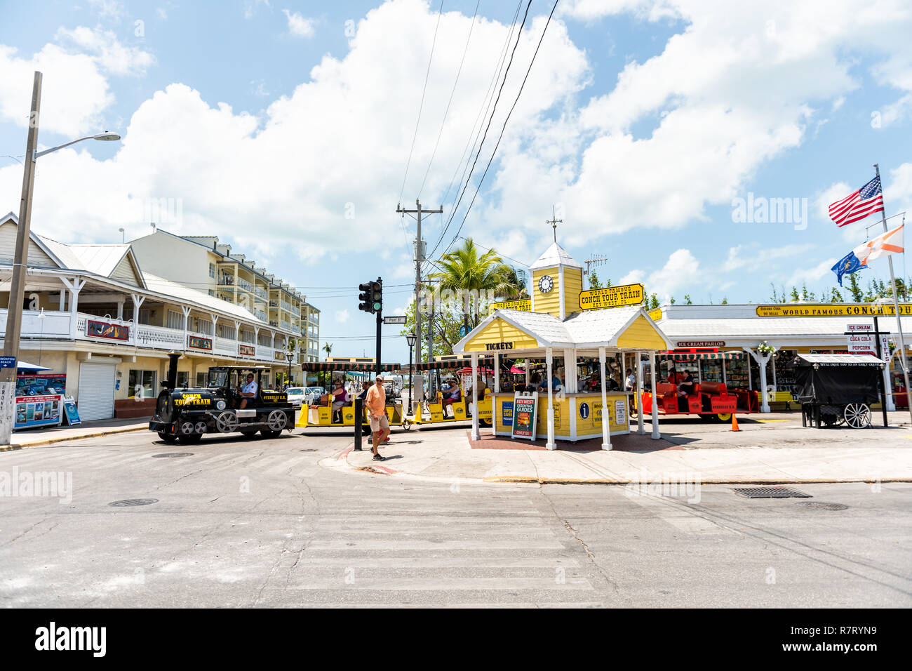 Key West, USA - May 1, 2018: People riding yellow color tour bus trolley with tourists at street road in Florida island on travel, sunny day, Conch Tr - Stock Image