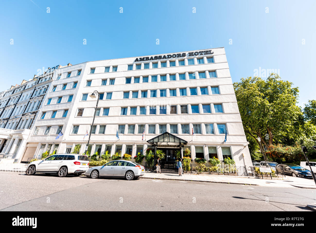 London, UK - September 13, 2018: Neighborhood district of Kensington, street, brick architecture, sign for Ambassadors hotel wide angle building - Stock Image
